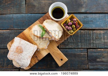 Pickled olives with bread and olive oil on chopping board