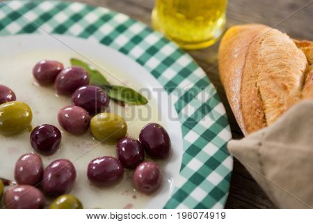 Close-up of marinated olives with oil and bread