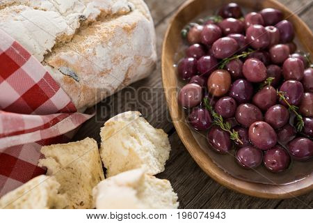 Close-up of marinated olives with bread loaf on wooden table