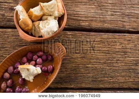 Marinated olives and bread pieces in bowl on wooden table