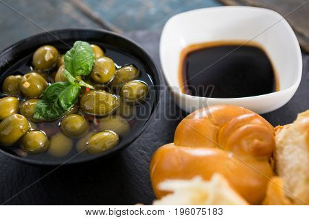 Marinated olives with bread pieces and olive oil on platter