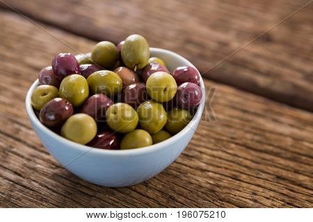 Marinated olives in white bowl on wooden table
