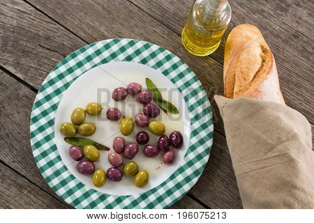 Marinated olives with oil and bread on wooden table