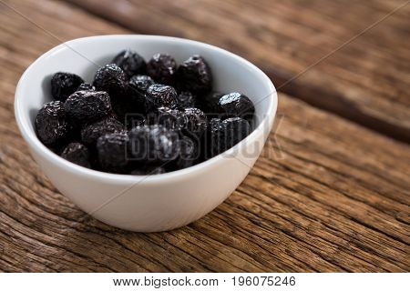 Dry olives in white bowl on wooden table