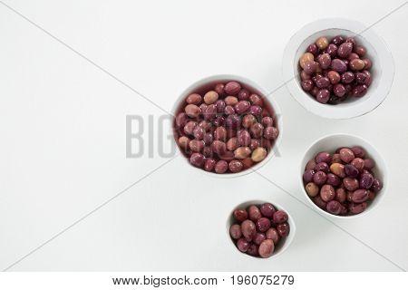 Pickled olives in bowls on white background