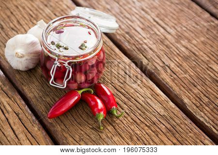 Pickled olives with ingredients on wooden table