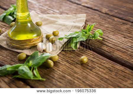 Close-up of olive oil and ingredients on wooden table