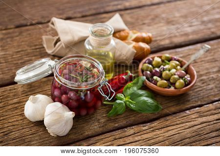 Pickled olives with ingredients and bread on wooden table