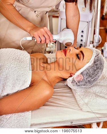 Ultrasonic facial treatment on ultrasound face machine. Woman receiving electric lift massage at spa salon. Electronic stimulation female muscles microcurrent therapy . Technologies of rejuvenation.