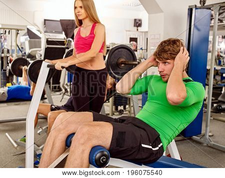 Tired sport man working his body by barbell in sport gym. He sitting on bench with barbell in sport gym. Couple in love train together.