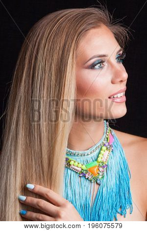 beautiful young blonde blue eyes woman beauty portrait with attractive large blue necklace with fringe studio shot