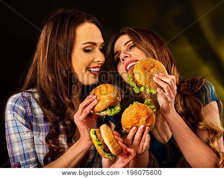 Hamburger fast food with ham and group people. Good Fast food concept. Friends two women eating sandwich junk in party. Girls eat up after diet.
