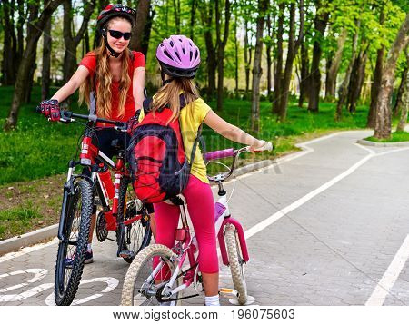 Bicycle path and sign with children. Girls wearing bicycle helmet with rucksack ciclyng ride. Kids are on white bike lane . Alternative to urban transport. Oncoming traffic. Summer vacation.