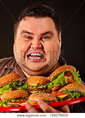 Fat man eating fast food hamberger and carries treat for friends on tray. Breakfast for overweight person. Junk meal leads to obesity. Man loves semi-finished products.