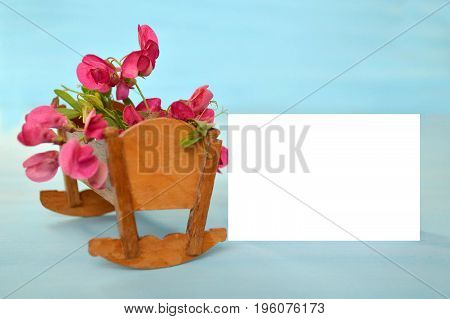 Blank baby girl card with cradle full of pink flowers