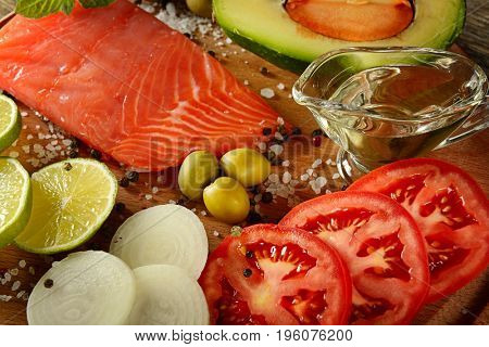 Meat red salmon fish, tomatoes, spices, green olives and olive oil on kitchen table. Top view. Selective focus.