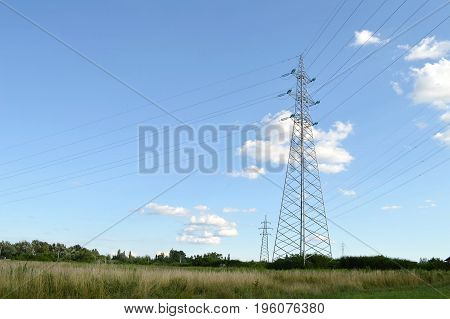 Electricity poles in the countryside and sky in background