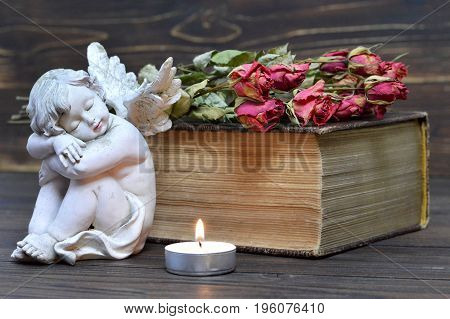 Angel candle and dry flowers on wooden background
