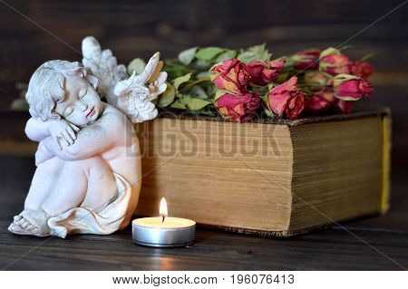 All Saints Day theme with angel figurine, burning candle and bunch of dry roses