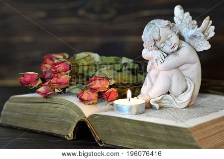 Angel candle and dry roses on wooden background