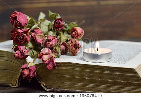 lose up of burning candle and dry roses
