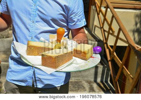 Man holds a platter with different types of cheeses