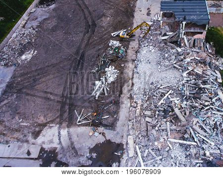 A process of buliding demolition, demolition site with heavy bulldozer and excavator with crushing equipment at work, demolished house, shot from air with drone