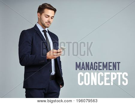 Management concepts. Young businessman with phone on color background
