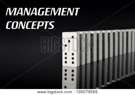 Management concepts. Dominoes on black background