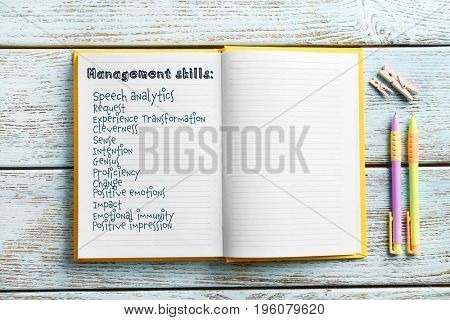 List of MANAGEMENT SKILLS written in notebook on wooden background
