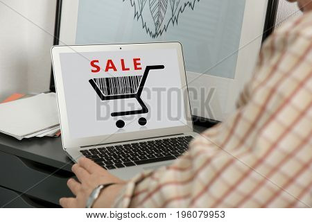 Internet shopping concept. Man using laptop at home