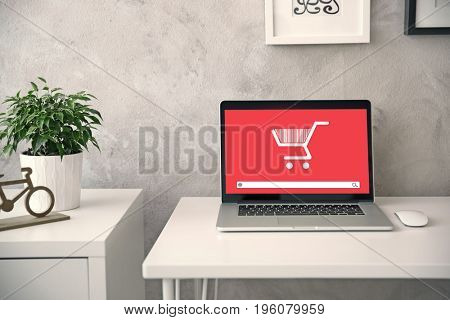 Internet shopping concept. Laptop with icon of market trolley and search bar on table at home