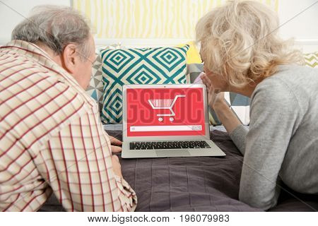 Internet shopping concept. Senior couple using laptop at home