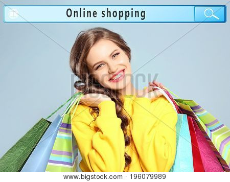 Young woman with paper bags and text ONLINE SHOPPING in search bar of internet browser on color background