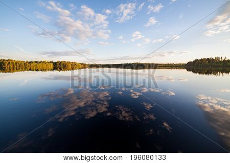 Still lake perfect reflection of sky and clouds at summer evening Finland