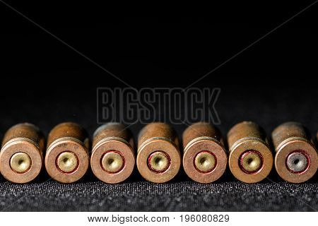 Lined in a straight row of empty shells of 9 mm pistol close up on the fabric