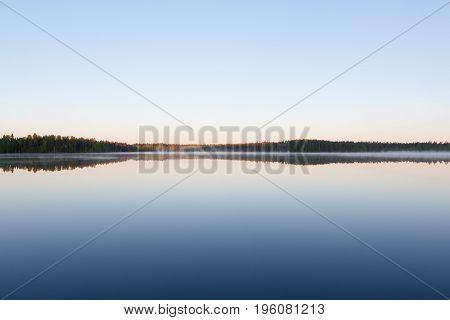 Still lake perfect reflection of sky at summer morning Finland