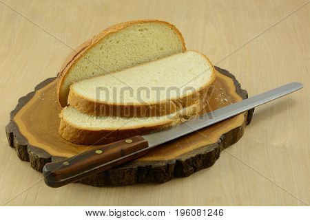 Lemon white chocolate bread loaf and slices on cutting board with bead knife