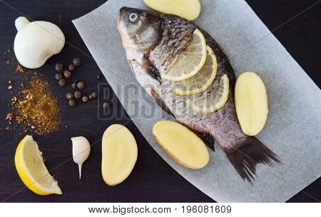 fresh river fish and potatoes lemon on the paper on a black background
