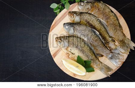 fried river fish with lemon lies on the Board on a black background