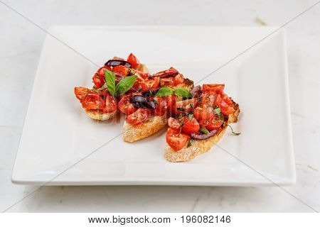 Italian bruschetta with chopped tomatoes, basil and olive in white plate on marble serface.