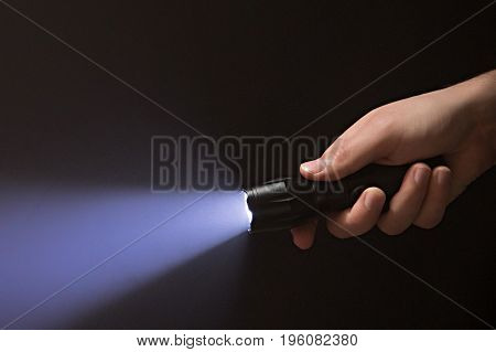 Black flashlight with purple beam in male's hand isolated on black background