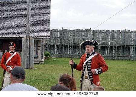 MACKINAW CITY, MICHIGAN / UNITED STATES - JUNE 18, 2017: Visitors listen to a lecture by a costumed interpreter on the parade ground of Fort Michilimackinac, in the Colonial Michilimackinac State Park.
