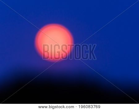 Abstract moonrise, defocused and taken at blue hour
