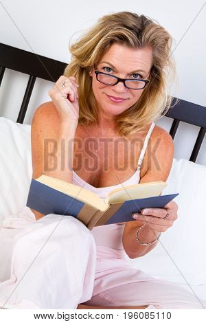 Senior woman reading book in bed