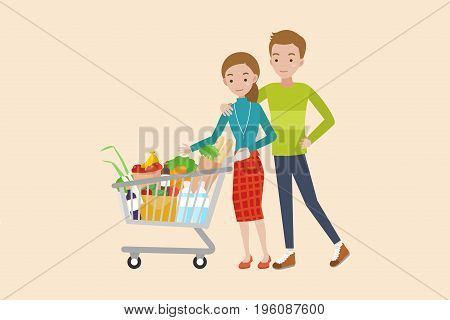 Young couple pushing a shopping cart full of groceries.