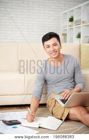 Happy Asian businessman sitting on the floor counting business expenses