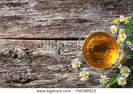 Cup of medicinal chamomile tea on wooden