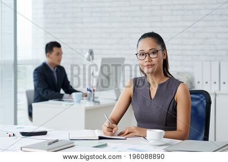 Pretty business lady in glasses taking notes in her notepad