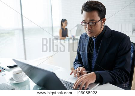 Vietnamese businessman with laptop concentrated on work